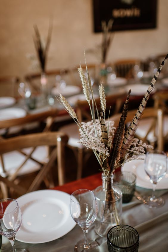 a stylish boho wedding centerpiece of feathers, wheat and some blooms in a clear vase is a very refined idea