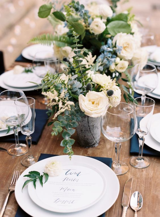 a stylish wedding tablescape with navy napkins, white porcelain, chic white floral and greenery centerpieces and silver