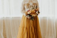 a sunshine yellow A-line wedding dress with a pelated skirt and a white lace op with long sleeves over it