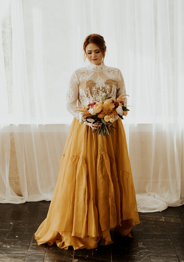 a sunshine yellow A line wedding dress with a pelated skirt and a white lace op with long sleeves over it