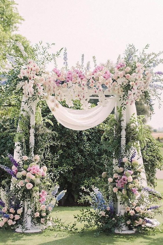 a super lush spring wedding arch decorated with white fabric, white, pink, blue and purple blooms and much greenery