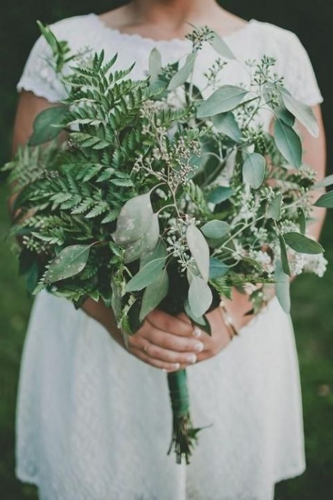 a very lush wedding bouquet of evergreens and eucalyptus for a casual bride