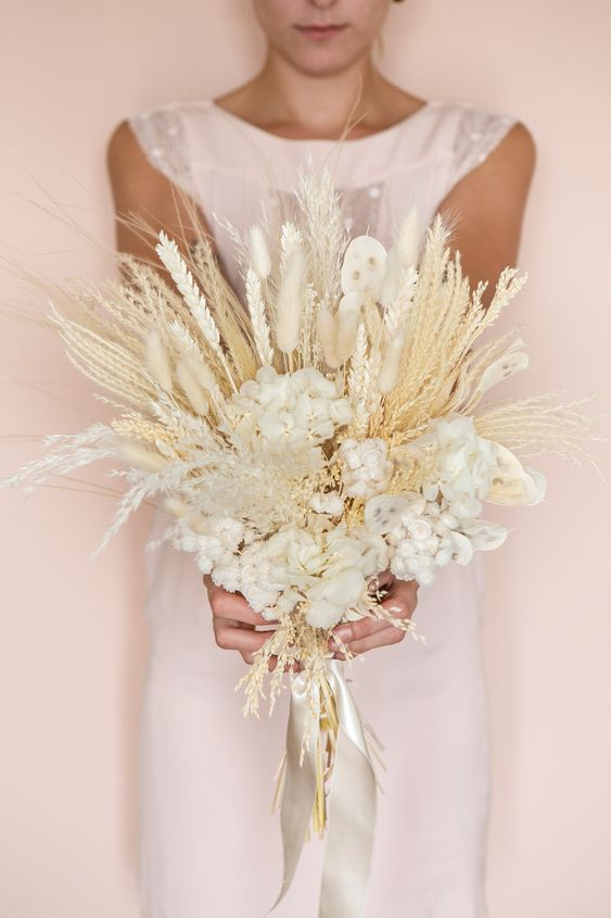 a wedding bouquet of white hydrangea, white pope's coin, immortal flowers, wheat, phalaris, miscanthus, grass, stipa, natural pampa herbs