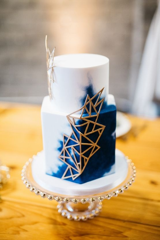 a white and navy watercolor wedding cake with gold geometric detailing for a chic look