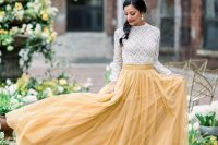 a white crochet lace top with a high neckline and long sleeves, a yellow pleated skirt for a bright and fun look
