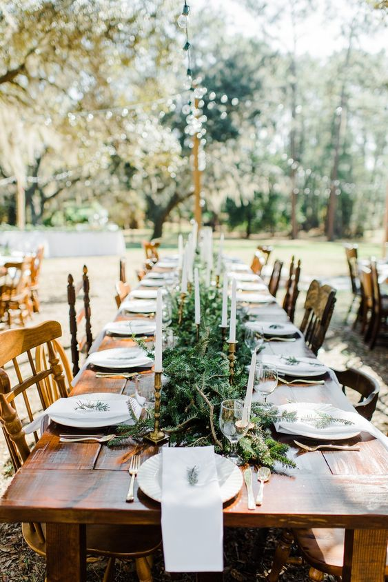 a winter backyard tablescape with an evergreen runner, tall candles and neutral linens and plates is a cool and chic idea
