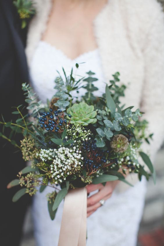 a winter wedding bouquet composed of greenery, succulents, berries and small white blooms plus long ribbons