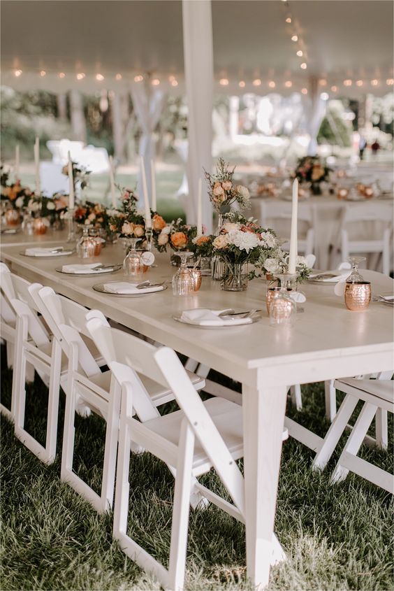 an elegant and chic backyard wedding tablescape with copper mugs, elegant tall candles, neutral and orange blooms and neutral linens
