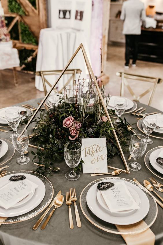 a 3D triangle with textural greenery and pink blooms and some floatign candles inside the centerpiece
