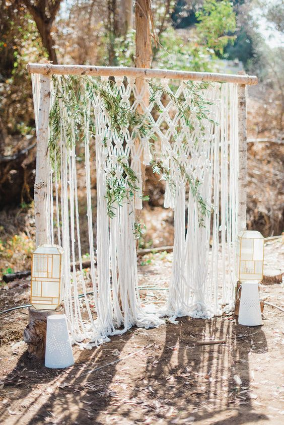 a backyard boho wedding arch decorated with greenery and macrame, with candle lanterns is a lovely idea for a backyard wedding