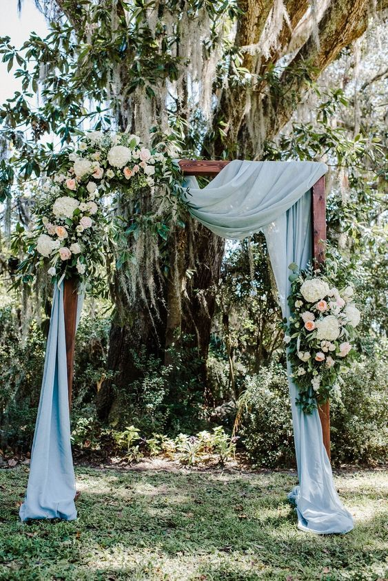 a backyard wedding arch covered with blue fabric, with neutral and pastel blooms and greenery is great for a romantic wedding