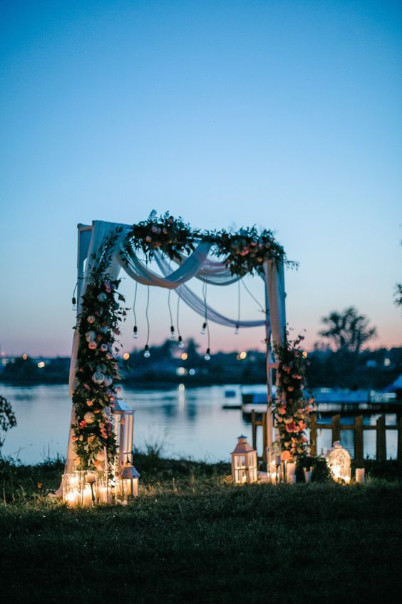 a backyard wedding arch decorated with white fabric, pastel blooms and greenery, lights and candle lanterns on the ground