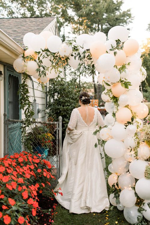 a backyard wedding arch made of blush blooms and greenery is a fun and cheerful idea that won't break the bank