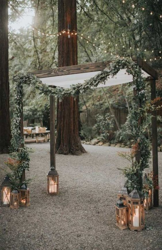 a backyard wedding arch with white fabric and a greenery garland plus rustic candle lanterns on the ground