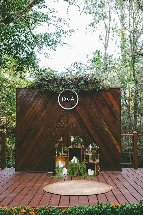 a backyard wedding backdrop of stained wood, with lush greenery and dark blooms and candles and floral arrangements by the wall