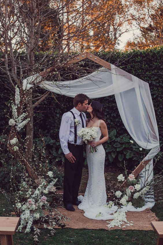 a beautiful and creative wedding arch of wood, with white fabric, blooming branches and petals on the rug is chic and romantic