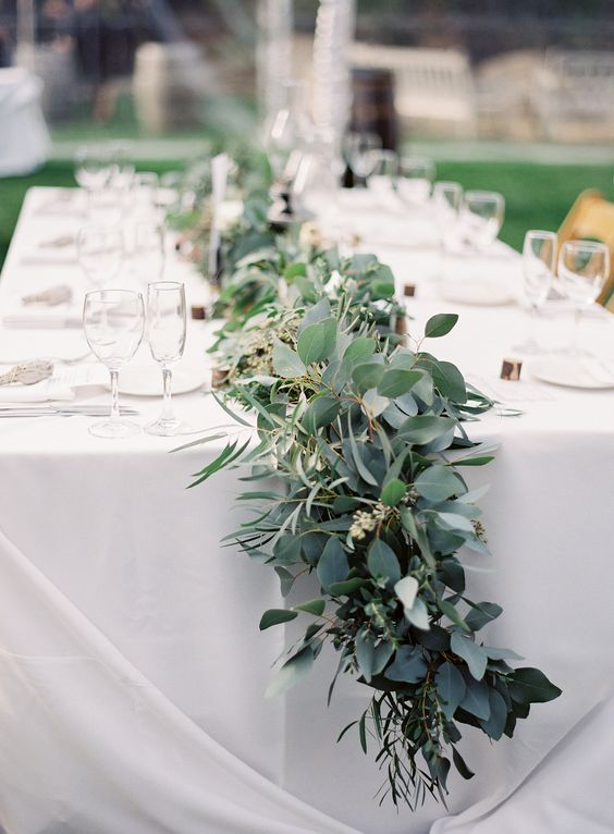 a beautiful and lush greenery garland refreshes the neutral tablescape and gives it a festive look