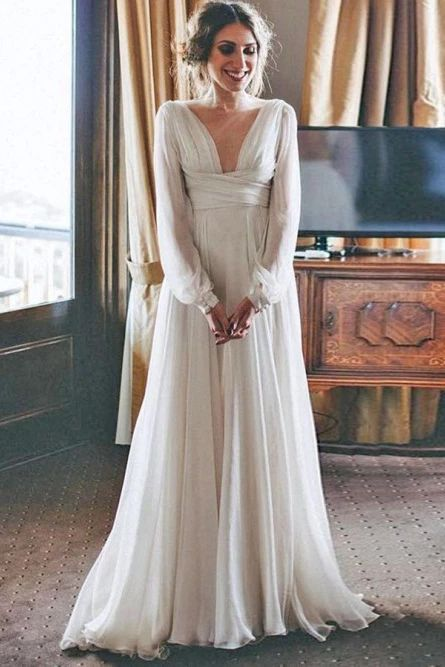 a beautiful and simple empire waist wedding dress with a draped bodice, a plunging neckline, long sleeves and a pleated skirt