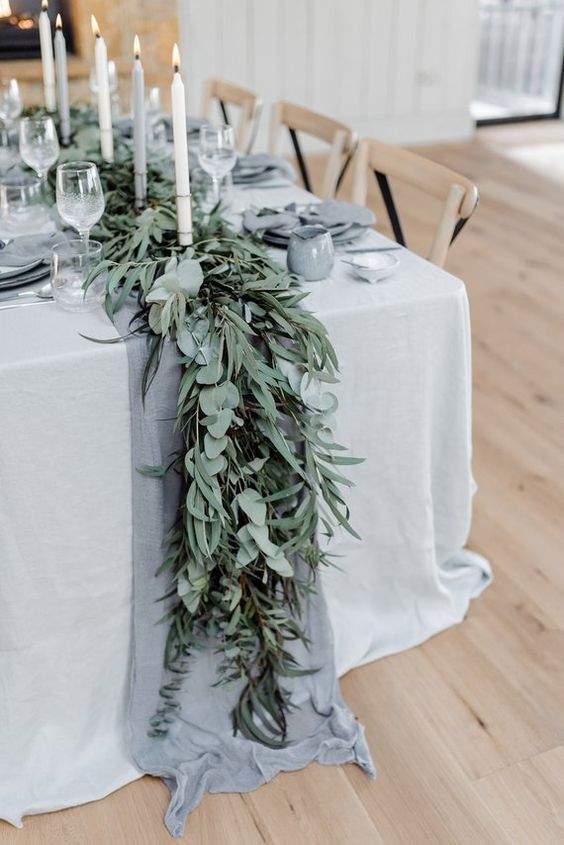 a beautiful greenery wedding table runners of various kinds of eucalyptus, with a grey runner and candles