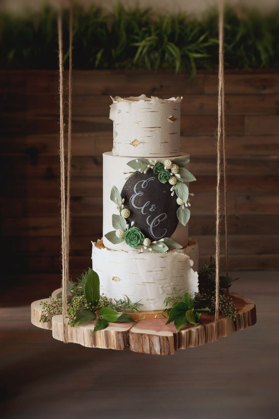 a birchbark wedding cake with a chalkboard part, sugar leaves and blooms is a nice rustic wedding dessert
