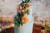 a blue and pink wedding cake with a watercolor effect, bright blooms and greenery for a summer boho wedding