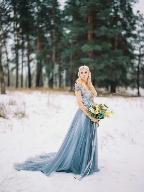 a blue wedding dress with an embellished bodice, short sleeves and a train plus a crystal chain headpiece