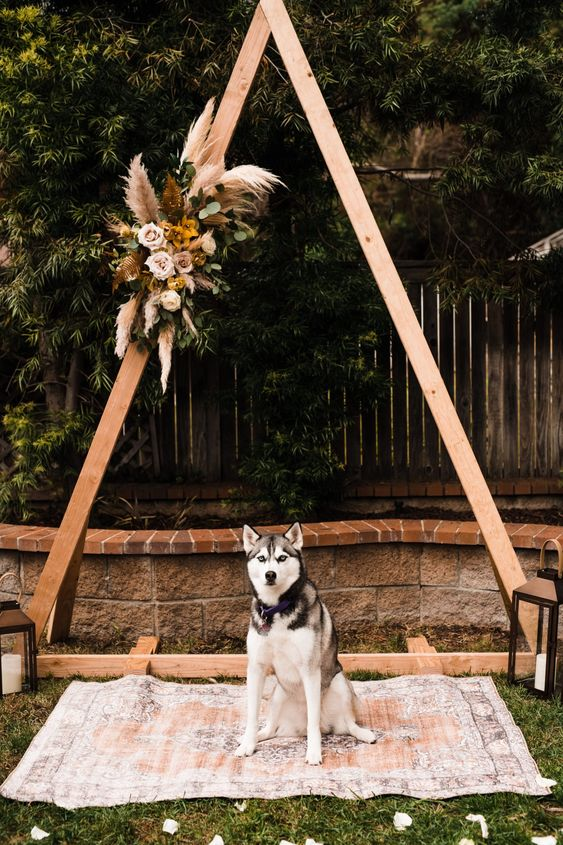 a boho backyard wedding arch decorated with greenery, pampas grass and bold blooms plus a boho rug for a backyard wedding