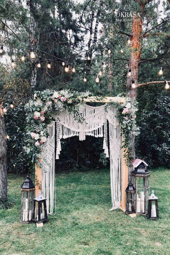 a boho backyard wedding arch decorated with macrame, with greenery, white and pastel blooms and candle lanterns on the ground