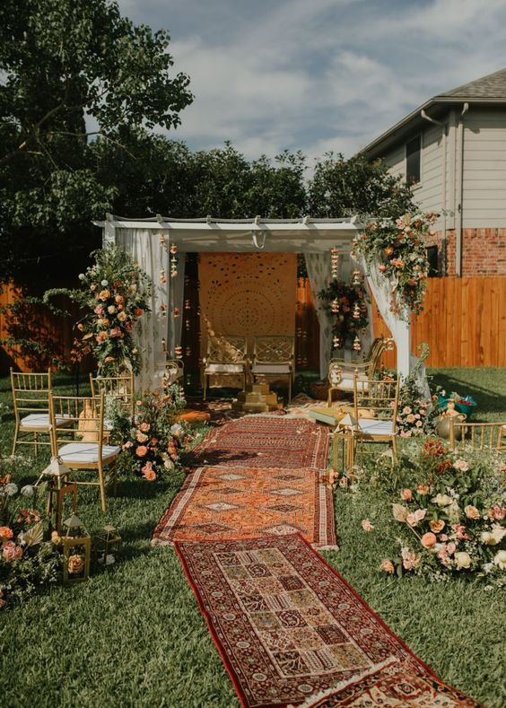 a boho backyard wedding ceremony space done with boho rugs, muted color blooms and greenery, with lovely gilded chairs and florals