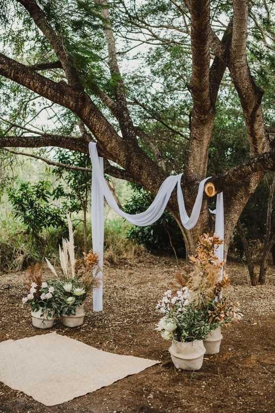 a boho backyard wedding ceremony space with white fabric on the branches, greenery, blooms and grasses in baskets and a rug