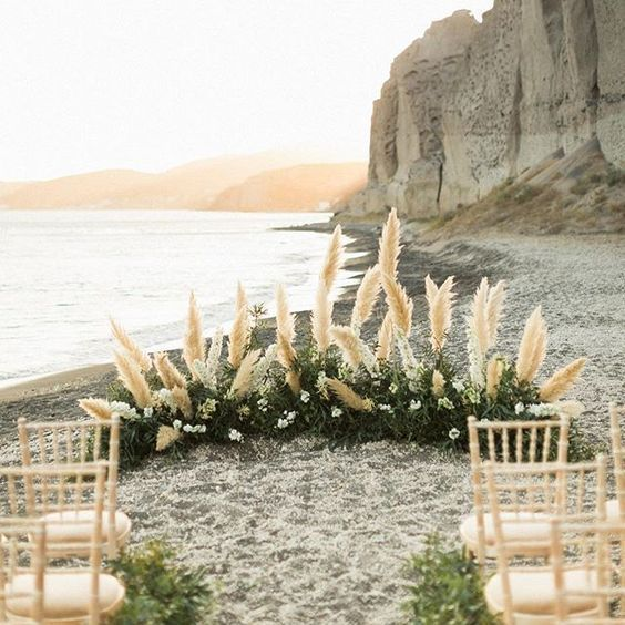 a boho beach wedding altar with greenery, white blooms and pampas grass plus simple chairs
