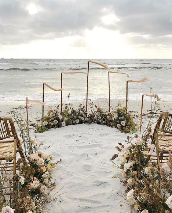 a boho beach wedding ceremony space done with lots of dried blooms, white and blush florals, flags and wicker chairs