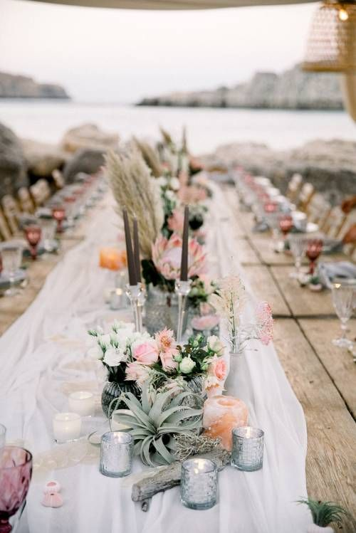 a boho beach wedding reception table decorated with air plants, pastel blooms, pampas grass, candles and elegant candle holders