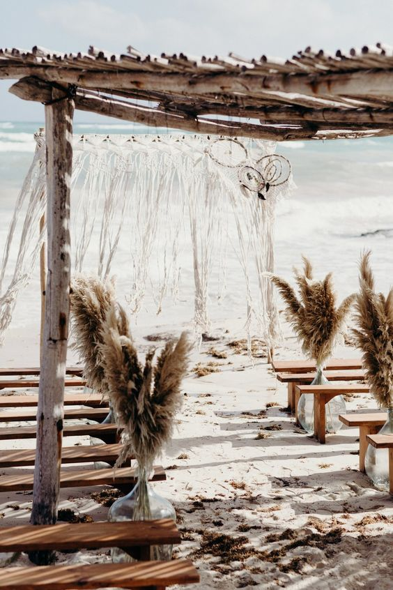 a boho beach wedding space with pampas grass in vases, wooden benches and a wedding arch with dream catchers and macrame