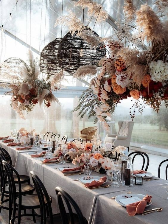 a boho chic tablescape done in rust and blush shades with lush florals on the table and over it, wicker lamps, colored napkins and candles