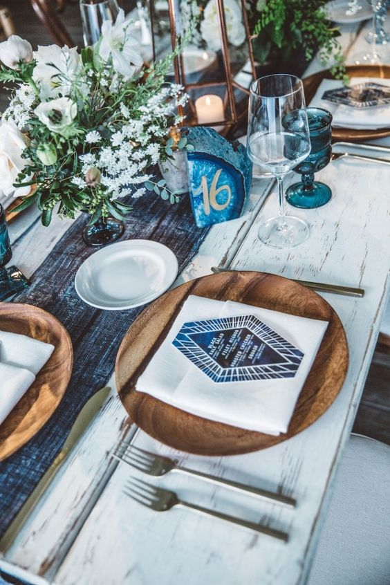 a boho chic tablescape with a tie dye table runner, blue glasses and agates, wooden chargers and blooms