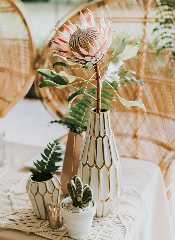 a boho desert wedding centerpiece with white vases, pots and greenery and a king protea