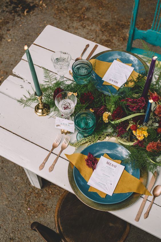 a boho gypsy tablescape with bright green and turquoise plates, colorful glasses and candles and lush florals and greenery