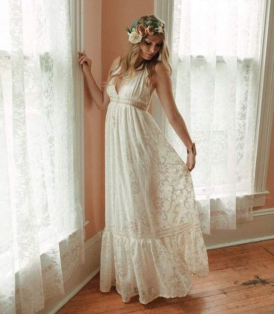 a boho lace A line wedding dress with a deep neckline, no sleeves and a floral crown for a hippie bride
