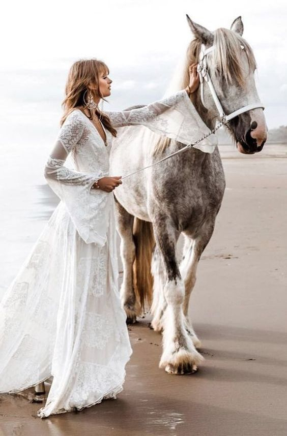 a boho lace wrap wedding dress with bell sleeves and a train plus statement earrings