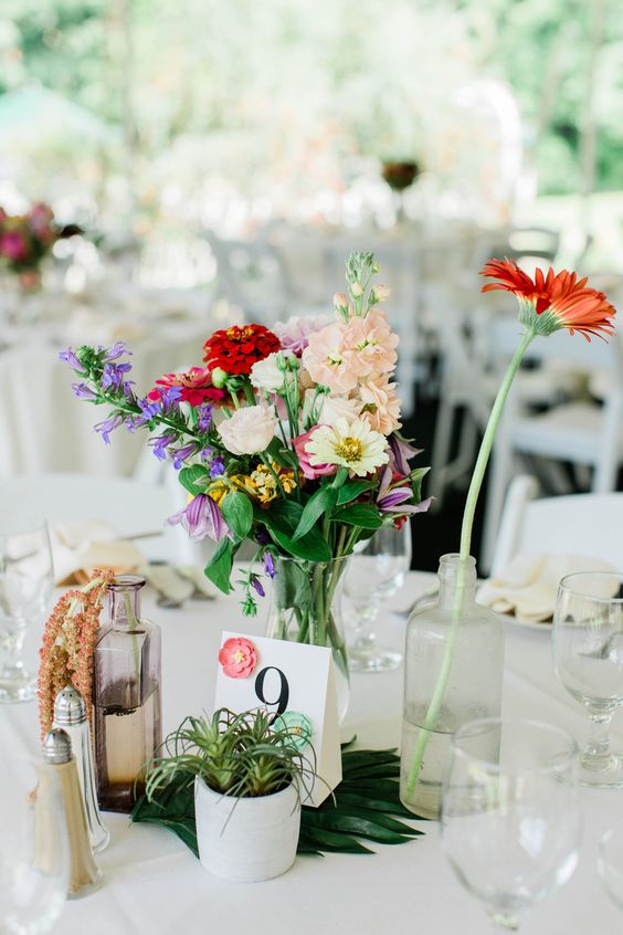 a boho summer wedding centerpiece with air plants, bright blooms, a monstera leaf and bottles and vases