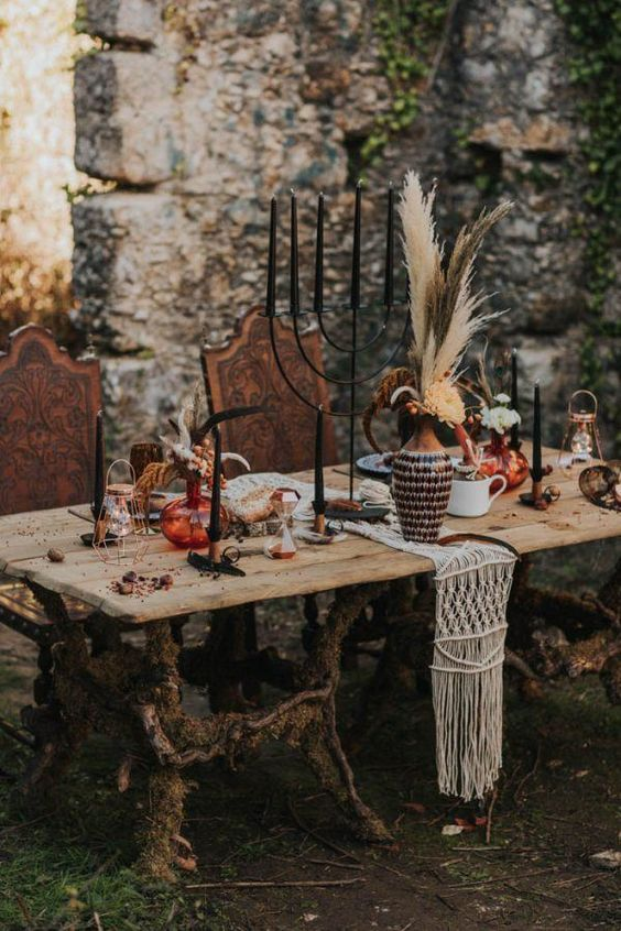 a boho table setting with a macrame runner, black candles, florals and pampas grass plus colored vases and glasses