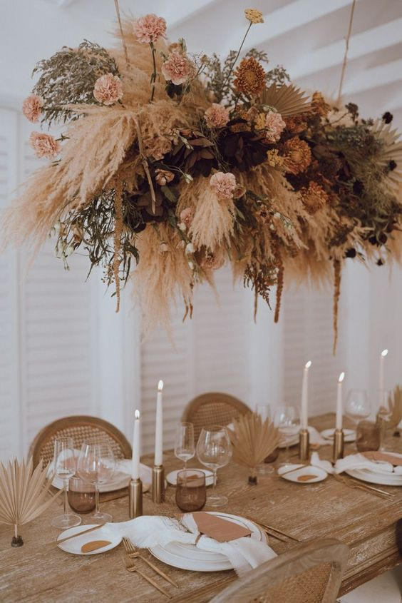 a boho tablescape done with gilded leaves, brown menus and neutral napkins plus an oversized dried floral and herbs installation