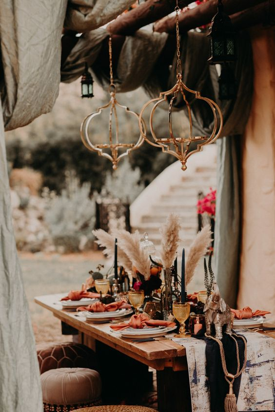 a boho tablescape with a velvet and tie dye runner, black candles, colored glasses, colorful napkins and pampas grass