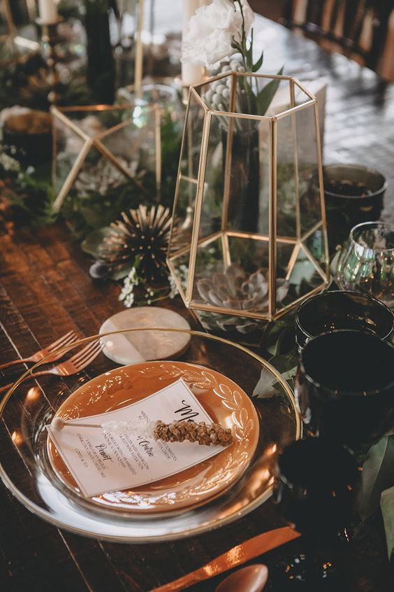 a boho tablescape with glass and porcelain plates, gilded terrariums with succulents and air plants, greenery and blooms