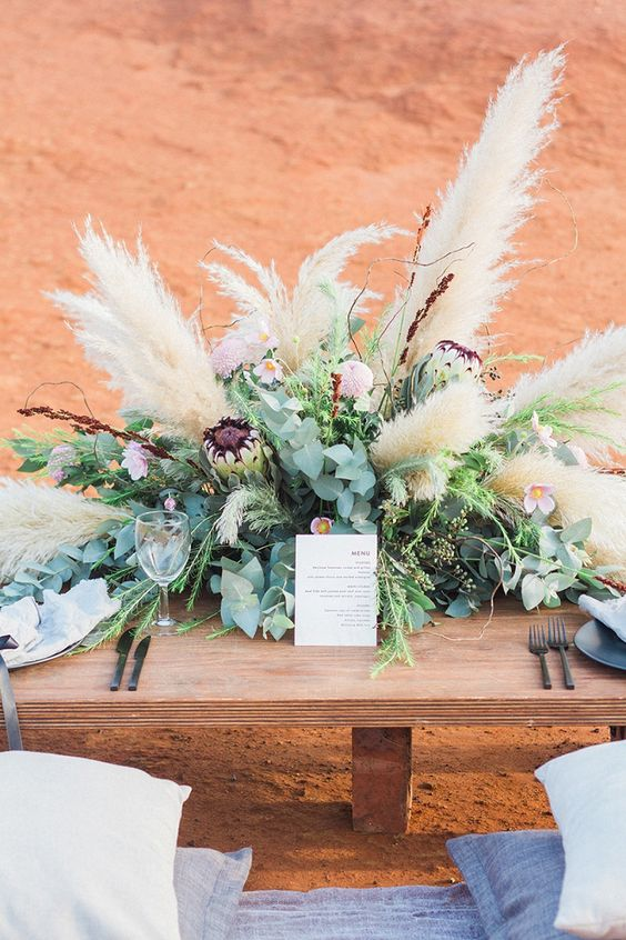 a boho wedding centerpiece of greenery, bright blooms and lush pampas grass