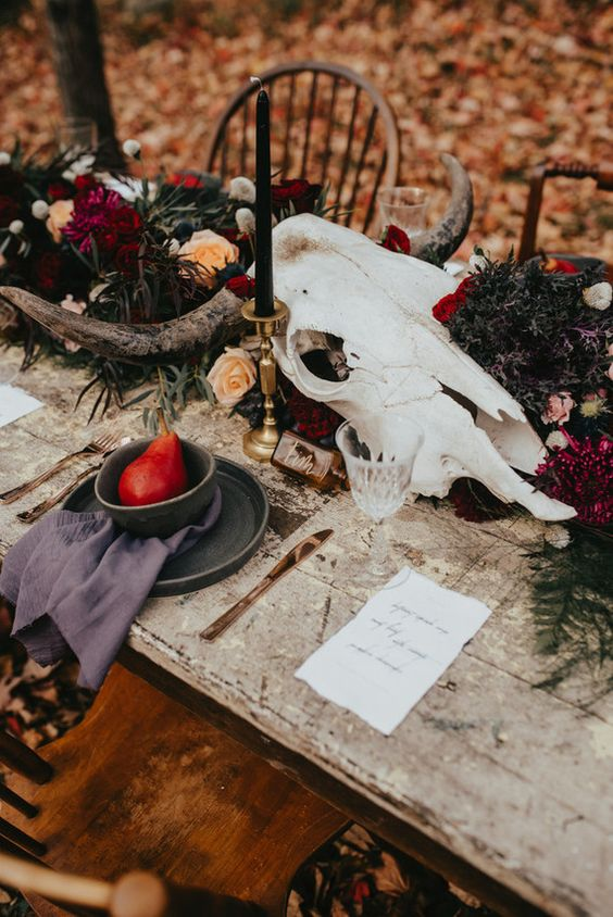 a boho wedding centerpiece with a skull, bright blooms, black candles and greenery
