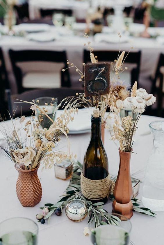 a boho wedding centerpiece with a twine wrapped bottle, copper vases, greenery, herbs and dried blooms
