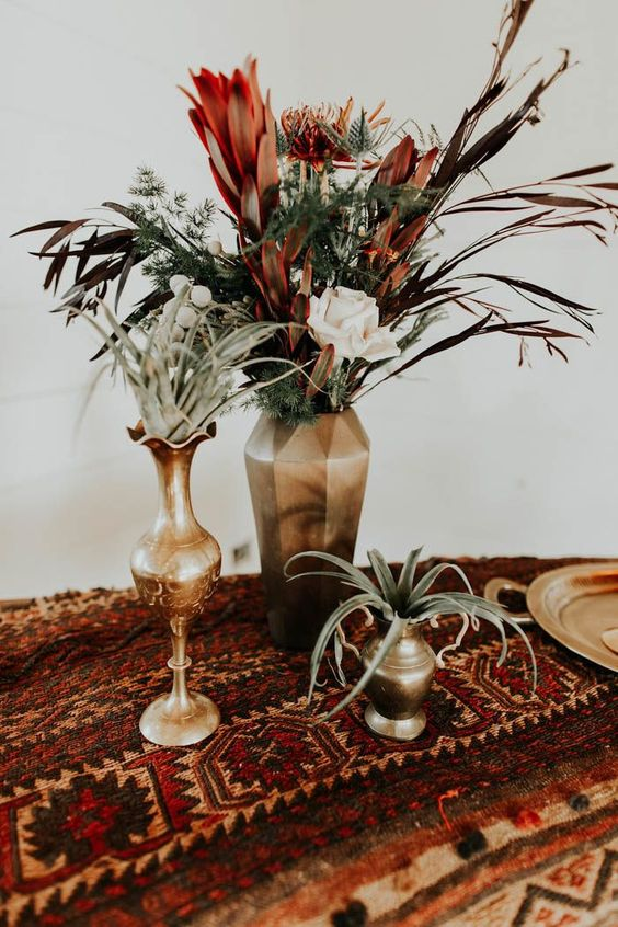 a boho wedding centerpiece with gold vases and pots, air plants, greenery, blush and rust-colored blooms