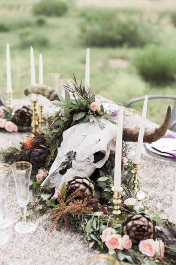 a boho wedding centerpiece with greenery, artichokes, blush blooms, candles and a large skull